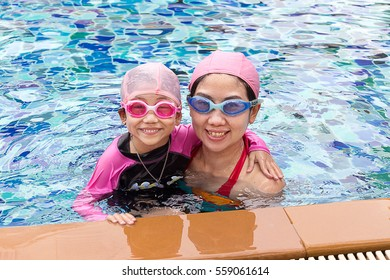 Happy family, young active mother and adorable little daughter having fun in a swimming pool enjoying summer vacation