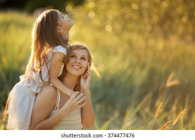 Happy family: a young beautiful pregnant woman and her little cute daughter walking together in the meadow on a sunny summer day. Nature in the country. Relationship between parents and children.
