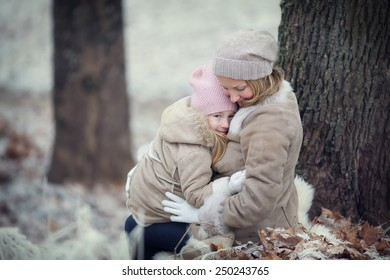 Happy family: a young beautiful woman with her little cute daughter walking in the winter city park.