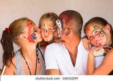 Happy family - young couple kissing younger baby daughter, after playing with paints