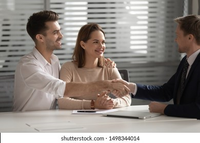 Happy family young couple shaking hands with financial advisor, lawyer, realtor, broker, bank worker, thanking for consultation, accepting loan or medical insurance offer, buying services at office.