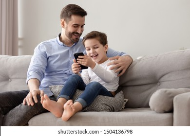 Happy family young dad and cute little kid child son sit on sofa relaxing having fun with mobile phone playing games watching funny social media videos laughing enjoying using cellphone at home