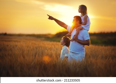 Happy family: young father with his little children walking in the wheat field at summer sunset. Girl is sitting on her daddy's shoulders and the man is pointing his daughter and son to something.