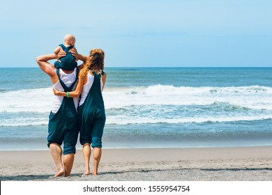 Happy family - young hipster father, mother, funny baby son walk together by tropical beach along sea surf. Little child sit on shoulders and have fun. Travel lifestyle, summer vacation with kids