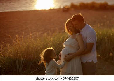 Happy family: young man, young beautiful pregnant woman and their cute little daughter walking along the sea on a Sunny summer day, the sunset. The relationship between parents and children.