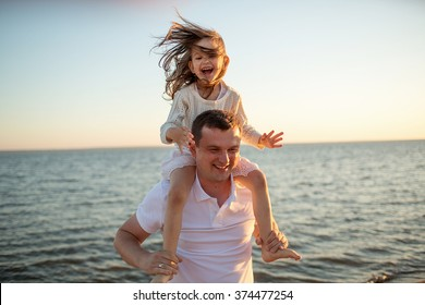 Happy family: the young man and his cute little daughter walking together on the sea in a summer Sunny day. Nature in the country. The relationship between parents and children.