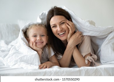 Happy family young mother and cute small kid daughter laugh look at camera covered with warm white duvet, smiling mom having fun with funny little child girl lay in cozy bed under blanket, portrait