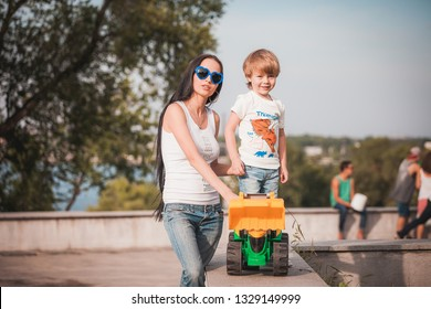 happy family young mother and her five year old son spending time outdoor on a summer day. Mother and son in green park standing with toy