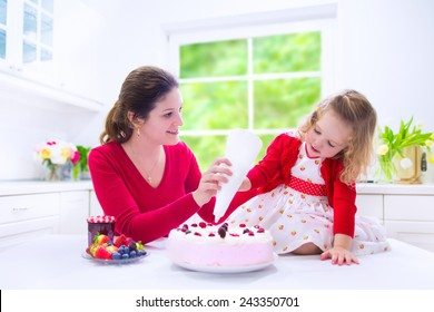 Happy family, young mother and her adorable little daughter, cute curly toddler girl in a red dress, baking fresh strawberry cream cake with fruit and berry in a white kitchen on a sunny summer day