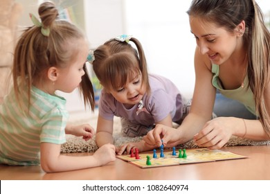 Happy family. Young mother playing ludo boardgame with her children daughters while spending time together at home.