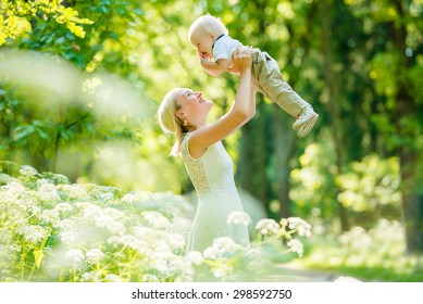 Happy family. Young mother throws up baby in the sky, on sunny day. Portrait mother and little son in the park. Positive human emotions, feelings, emotions.