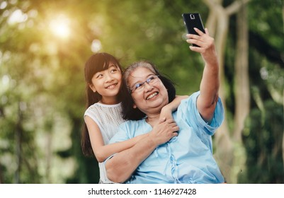 Happy family.Grandmother and granddaughter are taking selfie in park.