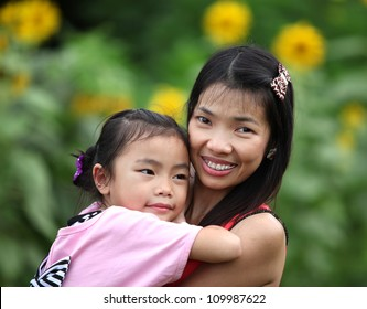 Happy familymom and baby playing against sumflower background in summer park