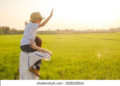 Happy fammily.A mother and son playing in grass fields outdoors at evening.Vacation and holiday concept with copy space