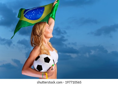 Happy fan of Brazilian football team, cheerful pretty girl on stadium cheering in support, holding up big national flag of Brazil, active people traveling to watch football games