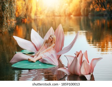 Happy fantasy young blonde woman little fairy princess sitting in pink lotus flower on lake water. Elf girl, with smiling face. Autumn nature background orange trees divine magic sun light. Pink dress