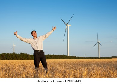 happy farmer (businessman) standing in wheat field over wind turbines background with his hands up and showing ok (thumbs up)