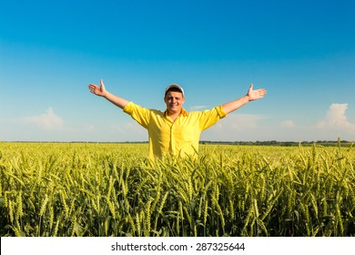 Happy farmer in field with handsup to a blue sky.