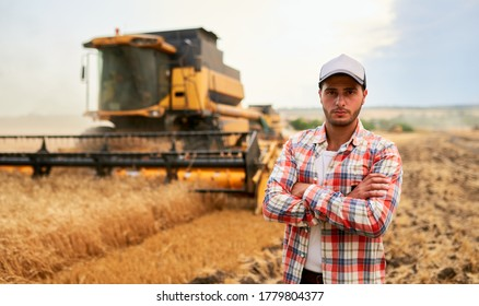 Happy farmer proudly standing in a field with arms crossed on chest. Combine harvester driver going to crop rich wheat harvest. Agronomist wearing flannel shirt, looking at camera on a farmland. - Shutterstock ID 1779804377