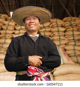 Happy farmer with stack hemp sacks