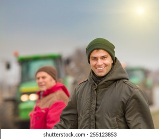 Happy farmer standing on farmland with tractors in background