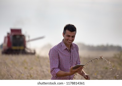 Happy farmer with tablet standing in soybean field during harvest