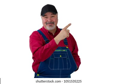 Happy farmer or worker in denim dungarees pointing upwards with a pleased smile towards blank copy space isolated on white