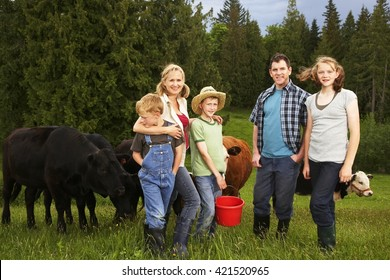 Happy farmers family in green field with cows in nature at the background