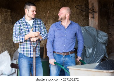Happy farmers working in a barn. One man is leaning on a pitchfork and another is pushing a wheelbarrow