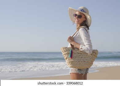 happy fashion blonde girl smiling portrait in the beach, wearing hat, a bag, shorts and white shirt, in the beach, profile photo