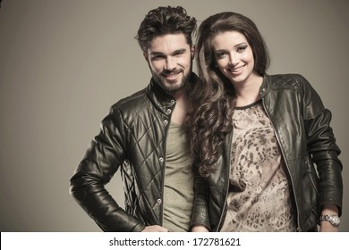 happy fashion couple in leather jackets smiling to the camera in studio