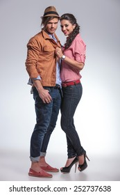 Happy fashion couple posing together on studio background. She is pulling his jacket.