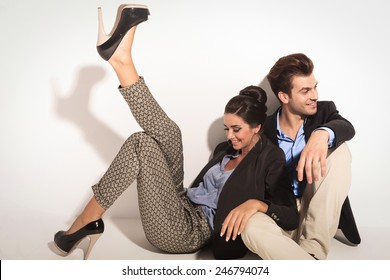 Happy fashion couple sitting together on the floor laughing while looking away from the camera. The woman is leaning on her lover while holding one leg up.
