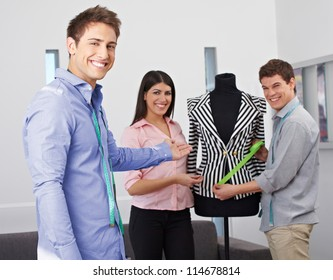 Happy fashion design students showing collection on a dress form