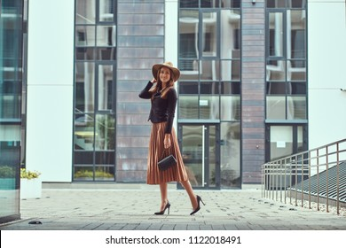 Happy fashion elegant woman wearing a black jacket, brown hat and skirt with a handbag clutch walking on the European city center.