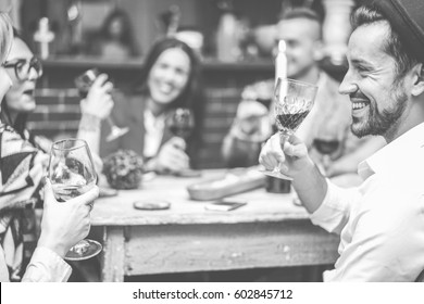 Happy fashion friends toasting wine in trendy cocktail bar restaurant - Young people having fun drinking and laughing together - Focus on right man mouth eye - Black and white editing - Warm filter