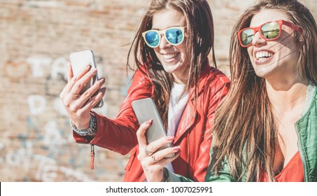Happy fashion friends watching videos on smartphone - Girlfriends having fun social technology trends outdoors - Friendship, youth lifestyle, millennials generation and tech concept