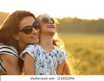 Happy fashion kid girl embracing her mother in trendy sunglasses and looking on nature background. Closeup portrait of happiness.