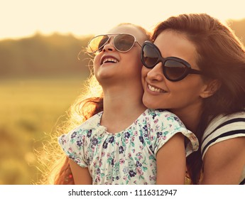 Happy fashion kid girl embracing her mother in trendy sunglasses and looking on nature background. Closeup portrait of joying family. Toned