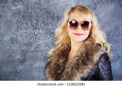 Happy fashion model posing in coat and sunglasses