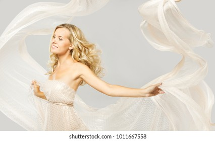 Happy Fashion Model in White Dress, Woman Beauty Portrait, Elegant Girl Dancing With Flying Flowing Fabric