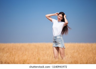 Happy fashion woman enjoying the life in the field. Nature beauty, blue sky and golden field with wheat. Outdoor lifestyle. Freedom concept. Woman in summer field of wheat