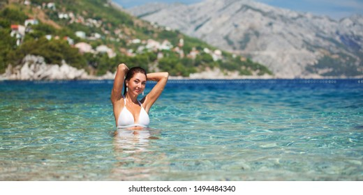 Happy fashion woman relax on the summer beach. Blue sky, beautiful mountains and crystal sea. Happy lifestyle. Vacation at Europe