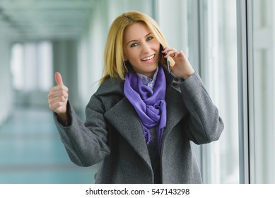 Happy fashion woman using smart phone and holding take away coffee in hall