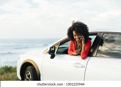 Happy fashionable afro hair woman in a car calling on cell phone towards the sea. Stylish black woman having fun during a trip to the coast.