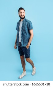 Happy fashionable handsome man with a beard posing standing on an isolated blue background
