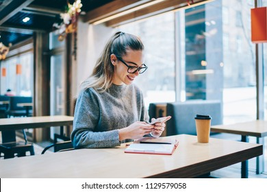 Happy fashionable hipster girl dialing number and checking positive email from followers in social networks, successful female journalist planning meetings using organiser on mobile phone indoors