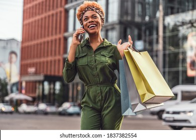 Happy fashionably dressed woman on the streets of the city while talking on her mobile phone. Shopping concept. Copy space