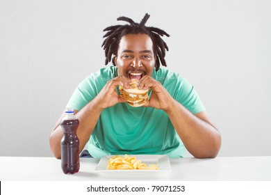 happy fat african american man eating a hamburger