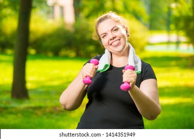 happy fat woman with dumbbells in the park during workout